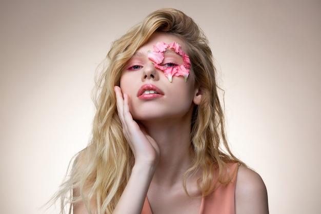 Maquiagem rosa. modelo atraente, loira e meiga usando um vestido rosa e maquiagem rosa