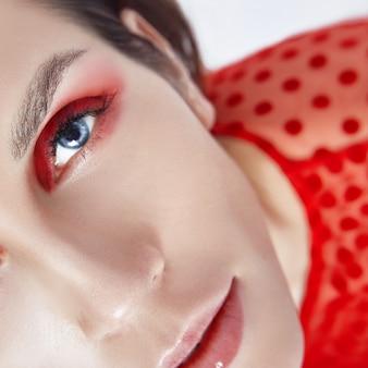 Maquiagem vermelha brilhante no rosto de mulher, cosméticos naturais