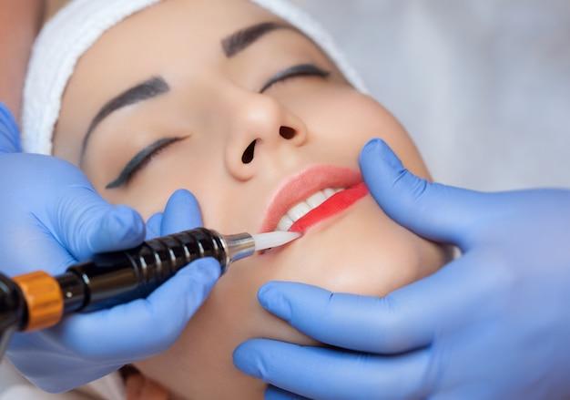Maquilhagem permanente para lábios vermelhos de mulher bonita em salão de beleza