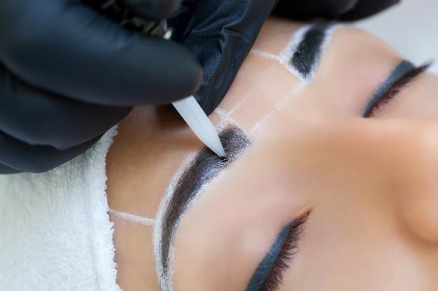 Maquilhagem permanente para sobrancelhas de mulher bonita com sobrancelhas grossas em salão de beleza