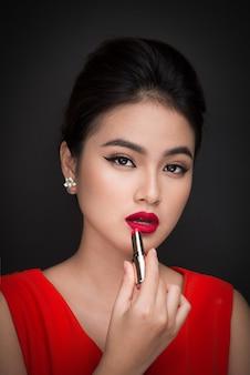 Maquilhagem profissional. modelo asiático atraente aplicando batom vermelho.