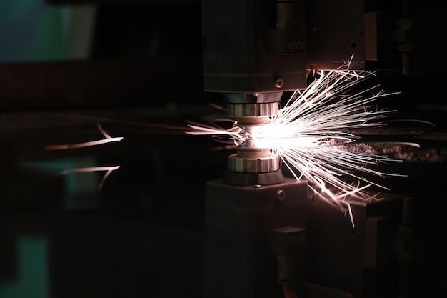 Máquina a laser cortando chapa de aço com faíscas brilhantes close up