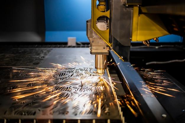 Máquina a laser industrial corta peças em chapa de aço.