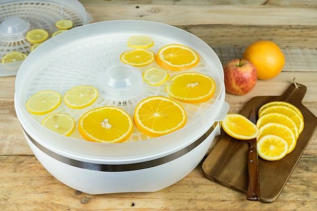 Máquina caseira para desidratar alimentos com rodelas de laranja na mesa da cozinha.