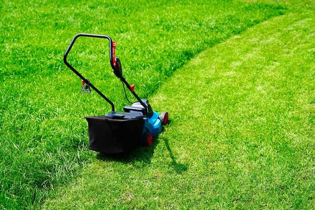 Máquina cortadora de grama elétrica aparando grama verde