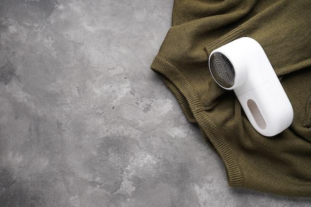 Máquina de barbear de tecido moderno e roupas em fundo cinza, espaço para texto, vista superior.