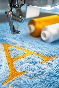Máquina de bordado e alfabeto logo na toalha