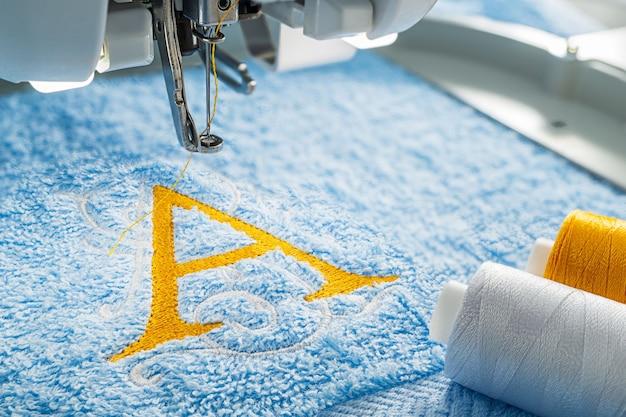 Máquina de bordar e desenho de alfabeto na toalha no aro