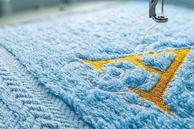 Máquina de bordar e desenho de alfabeto na toalha