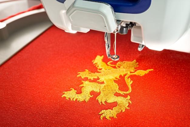 Máquina de bordar e design de leão de ouro na camisa de tecido de algodão vermelho