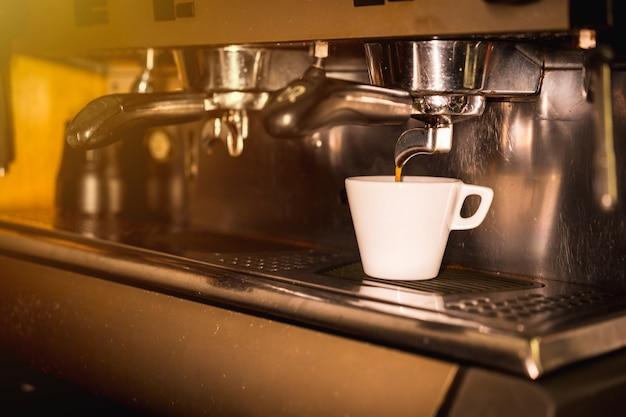 Máquina de café colocando um descafeinado em uma xícara branca