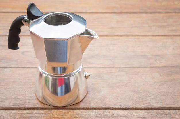 Máquina de café de metal na mesa de madeira
