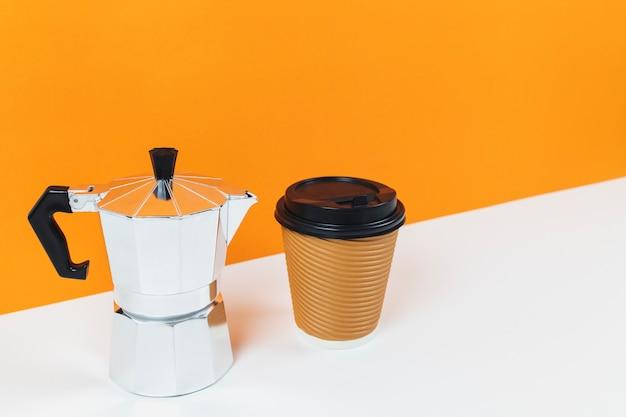 Máquina de café expresso de café com uma xícara de café de papel em uma mesa branca e fundo de parede laranja