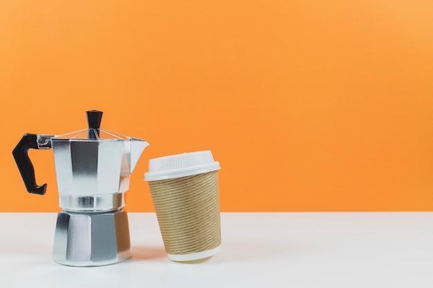 Máquina de café expresso de café com uma xícara de café de papel em uma mesa branca