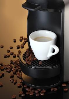 Máquina de café expresso e xícara de café na superfície marrom