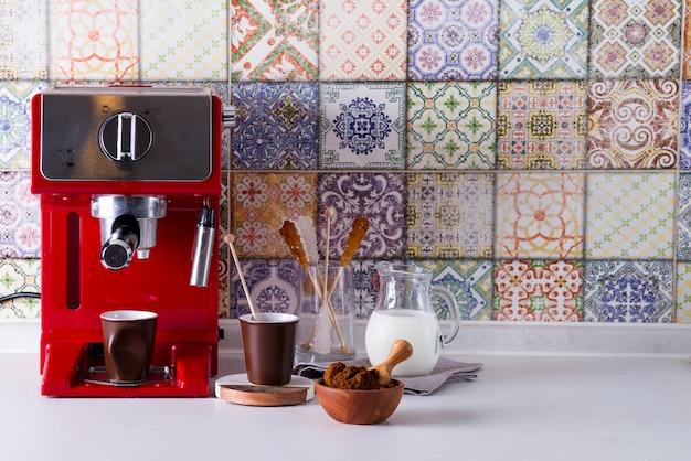 Máquina de café expresso em casa na bancada da cozinha com dois copos, leite e açúcar em palitos. fazendo café em casa.