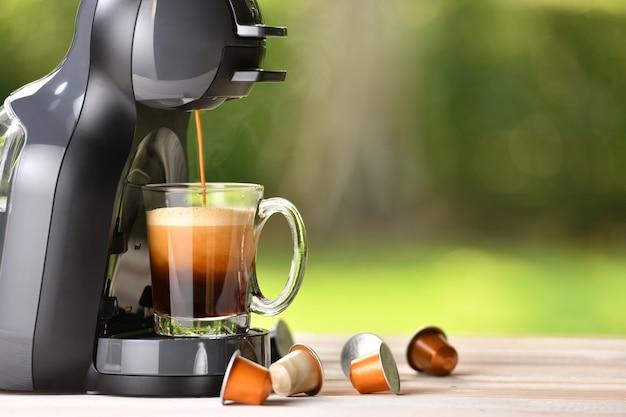 Máquina de café fazendo café com cápsulas na mesa de madeira