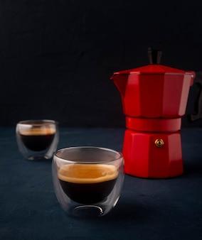 Máquina de café geyser e café em um copo de vidro sobre uma mesa de madeira no preto.