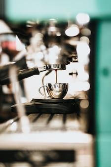Máquina de café grande metal derramando café em um copo de metal