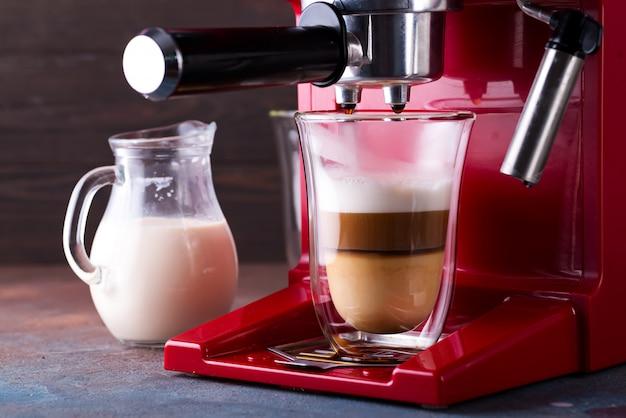 Máquina de café preparando café com leite fresco e derramando em vidro no restaurante, close-up