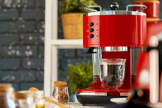 Máquina de café vermelha com um copo no balcão da cozinha