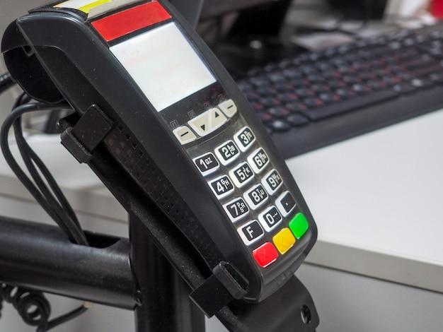 Máquina de cartão de crédito com fundo desfocado com computador e teclado