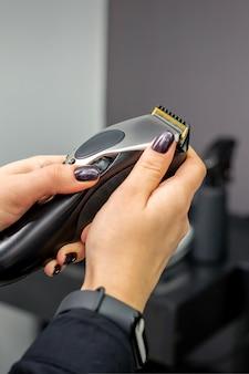 Máquina de cortar cabelo nas mãos de uma cabeleireira profissional ou barbeira em um salão de cabeleireiro