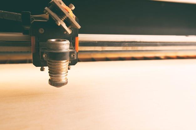 Máquina de corte a laser está cortando a prancha de madeira