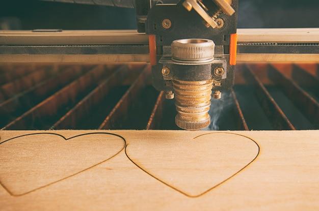 Máquina de corte a laser está cortando corações na prancha de madeira
