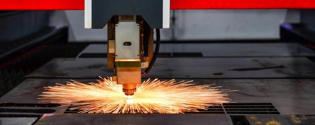 Máquina de corte a laser raytools enquanto corta a folha de metal com a luz de faísca na fábrica