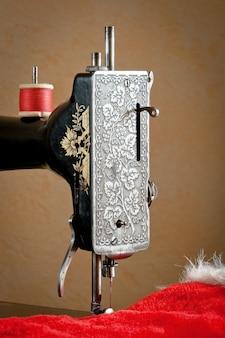 Máquina de costura antiga com fio vermelho
