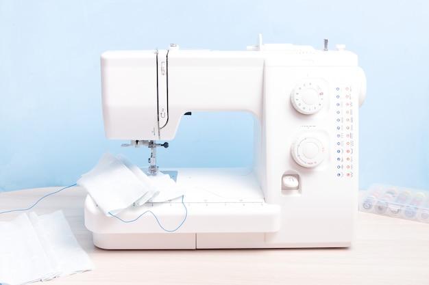 Máquina de costura branca, costure uma máscara facial de tecido em casa, parede azul