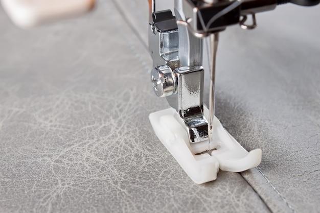 Máquina de costura com calcador especial faz costura em couro cinza. processo de costura de perto