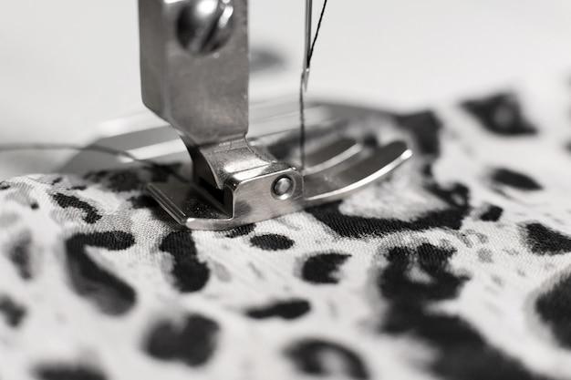 Máquina de costura com tecido e linha, closeup