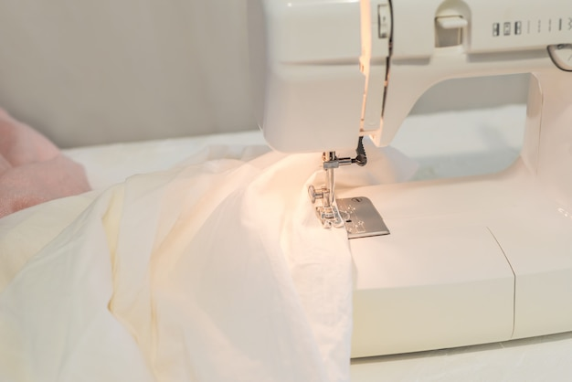 Máquina de costura, costura de tecido branco, alfaiate