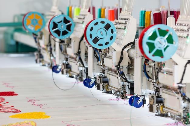 Máquina de costura de fábrica faz closeup de padrão de cor. tecido, ninguém. fabricação de costura, tecnologia de costura