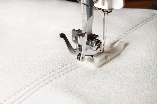 Máquina de costura e couro branco com um close-up da costura