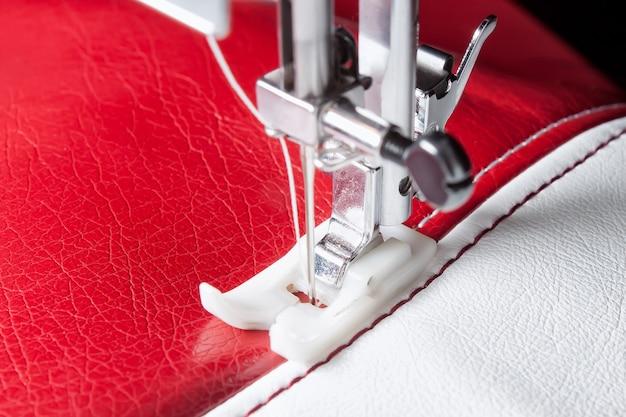Máquina de costura e couro branco e vermelho com um close-up da costura
