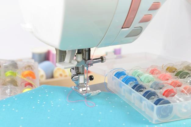 Máquina de costura e rolos de linha colorida, tesoura, tecido e acessórios para costura.