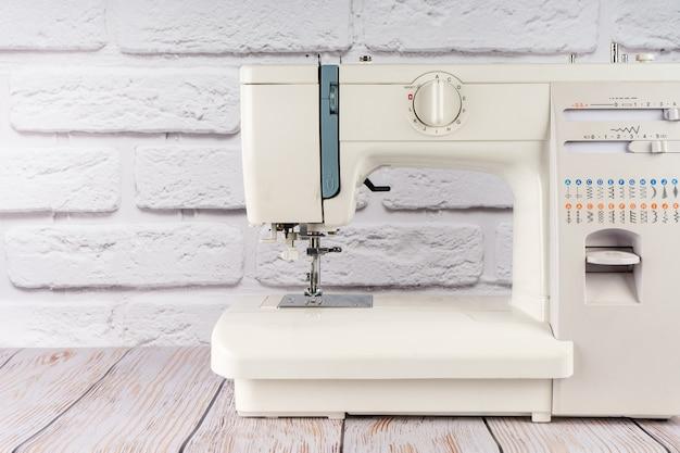 Máquina de costura moderna no fundo da parede de tijolo branco. copie o espaço para o texto.
