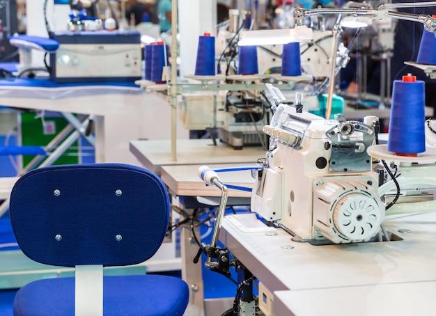 Máquina de costura, ninguém, roupas costuradas em tecido. produção fabril, fabricação de tecidos, local de trabalho da costureira