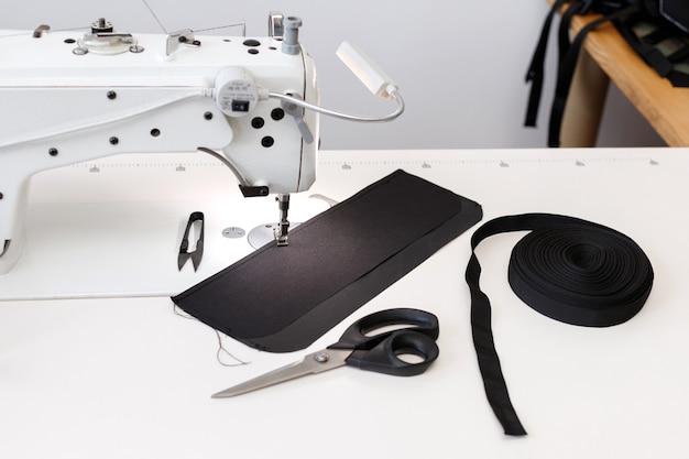 Máquina de costura no local de trabalho em um fundo cinza. fechar-se