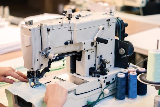 Máquina de costura overloque industrial e mãos de costureira trabalhando na fábrica de roupas