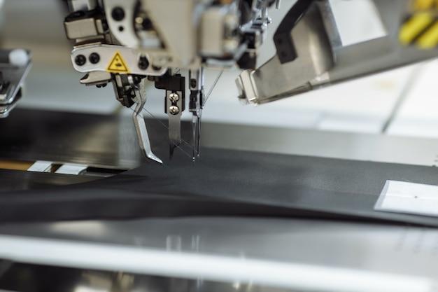 Máquina de costura rabiscando tecido sob medida na fábrica