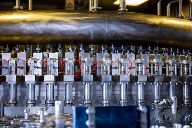 Máquina de enchimento automática derrama água em garrafas pet de plástico em uma fábrica de bebidas moderna