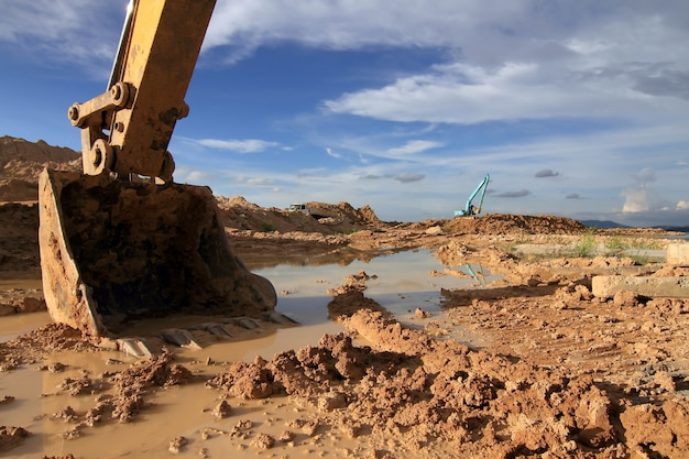 Máquina de escavadeira carregador durante a terraplenagem trabalha ao ar livre no canteiro de obras