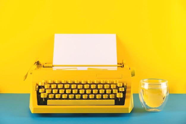 Máquina de escrever amarela brilhante em uma mesa amarela e azul ao lado de um copo d'água