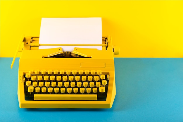 Máquina de escrever amarela brilhante em uma sala amarela e azul