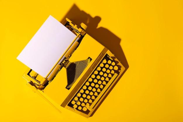 Máquina de escrever amarela brilhante na superfície amarela