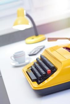 Máquina de escrever amarela com lâmpada e café na mesa de escritório branca perto da janela